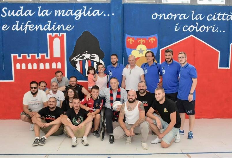 """La foto tra i tifosi rossoblù e il Presidente Notari con lo staff. Sullo sfondo il murales realizzato dai Gubbio Supporters al """"Barbetti"""""""